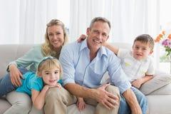 Lycklig familj som kopplar av på soffan royaltyfri foto