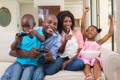 Lycklig familj som kopplar av på soffan som spelar videospel Arkivbild