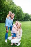 lycklig familj som kramar och ler på kameran, medan spendera tid tillsammans arkivfoton