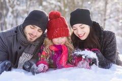 Lycklig familj som lägger på insnöad vinterskog arkivfoton