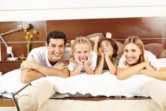 Lycklig familj som lägger på säng i sovrum Royaltyfri Bild