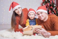 Lycklig familj som läser en bok med julsaga Royaltyfria Bilder