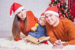 Lycklig familj som läser en bok med julsaga Royaltyfri Bild