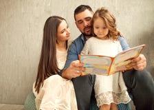 lycklig familj som läser en bok till hennes dotter dagblomman ger mödrar mumsonen till royaltyfri fotografi