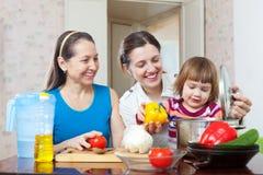 Lycklig familj som lagar mat tillsammans lunch Fotografering för Bildbyråer
