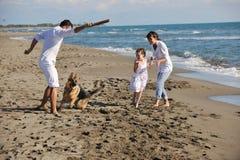 Lycklig familj som leker med hunden på strand Arkivbilder