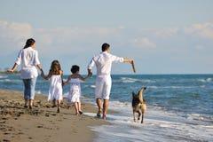 Lycklig familj som leker med hunden på strand Arkivbild
