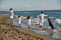 Lycklig familj som leker med hunden på strand Royaltyfria Foton