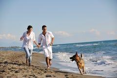 Lycklig familj som leker med hunden på strand Royaltyfri Bild