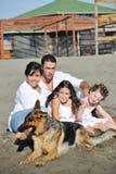 Lycklig familj som leker med hunden på strand Royaltyfri Foto