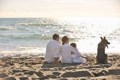 Lycklig familj som leker med hunden på strand Fotografering för Bildbyråer
