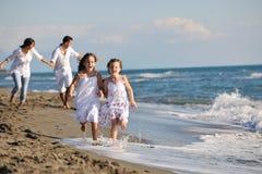 Lycklig familj som leker med hunden på strand Royaltyfri Fotografi