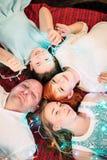 Lycklig familj som ler med girlanden för julljus nära julgranen Retuscherat skott av den bästa sikten arkivfoto