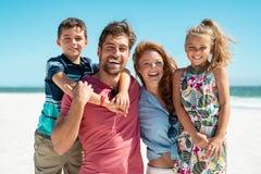 Lycklig familj som ler på stranden royaltyfri fotografi