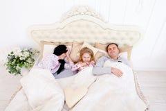 Lycklig familj som ligger i en vit säng och sömn Moder fader och Arkivbilder