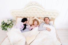 Lycklig familj som ligger i en vit säng och sömn Moder fader och Royaltyfria Foton