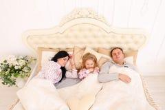 Lycklig familj som ligger i en vit säng och sömn Moder fader och Arkivfoto