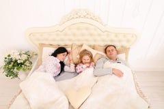 Lycklig familj som ligger i en vit säng och sömn Moder fader och Royaltyfri Fotografi