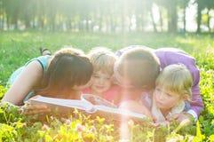 Lycklig familj som ligger på gräset och läsningen en bok royaltyfria bilder