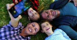 Lycklig familj som ligger på gräset och tar selfie arkivfilmer