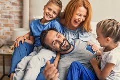 Lycklig familj som ner hemma ligger på säng royaltyfria foton