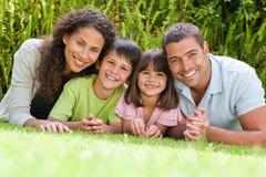 Lycklig familj som ner ligger i trädgården Royaltyfria Bilder