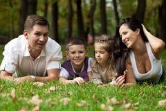 Lycklig familj som ner ligger i trädgården royaltyfri fotografi
