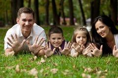 Lycklig familj som ner ligger i trädgården fotografering för bildbyråer