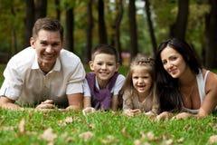 Lycklig familj som ner ligger i trädgården arkivfoton