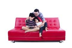 Lycklig familj som placeras på en isolerad soffa Arkivbild