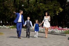 Lycklig familj som promenerar den förorts- gatan arkivfoton