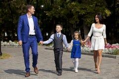 Lycklig familj som promenerar den förorts- gatan arkivbilder