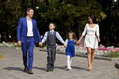 Lycklig familj som promenerar den förorts- gatan royaltyfri bild