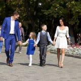 Lycklig familj som promenerar den förorts- gatan royaltyfri fotografi