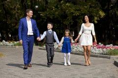 Lycklig familj som promenerar den förorts- gatan royaltyfria foton