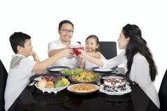 Lycklig familj som rostar exponeringsglas för matställe på studio Royaltyfria Bilder