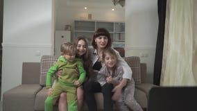 Lycklig familj som rotar för fotbollslaget som sitter på soffan Mamman och sonen smäller deras knä Lycklig familjferie stock video