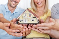 Lycklig familj som rymmer ett model hus Arkivbilder