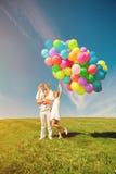 Lycklig familj som rymmer färgrika ballonger Mamma ded och daughte två royaltyfri bild
