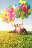 Lycklig familj som rymmer färgrika ballonger Mamma ded och daughte två arkivbild