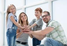 Lycklig familj som sätter deras handtogethe arkivbild