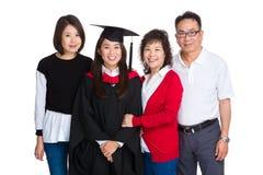 Lycklig familj som samlas samman med doktorand- stude Arkivfoto
