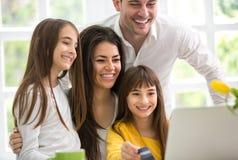Lycklig familj som ser bärbara datorn Royaltyfria Bilder