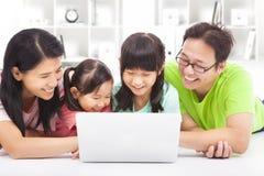 Lycklig familj som ser bärbara datorn Fotografering för Bildbyråer