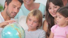 Lycklig familj som ser jordklotet Fotografering för Bildbyråer