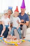 Lycklig familj som ser kameran på en födelsedag Arkivbild