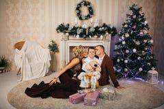 Lycklig familj som sitter nära julgranen Arkivbild
