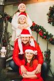 Lycklig familj som sitter nära julgranen I rött Arkivfoton