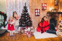 Lycklig familj som sitter nära julgranen I rött Arkivfoto