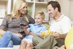 Lycklig familj som sitter på den hållande ögonen på televisionen för Sofa Royaltyfri Bild